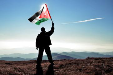 Successful silhouette man winner waving Jordan flag on top of the mountain peak
