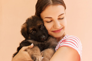Portrait of German shepherd puppy posing on woman's hands