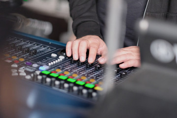 The sound engineer's hands on the mixing console during the concert
