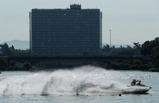 A jet ski rider performs on a lake in front of the Italian energy company Eni's headquarters in Rome