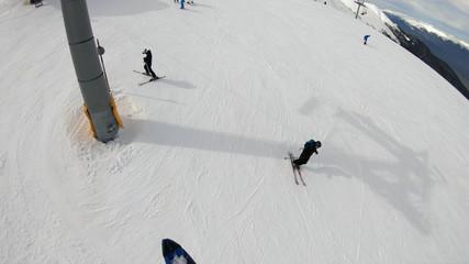 Winter alpine ski resort. Snow forest and skiers on a ski lift pov. Aerial view