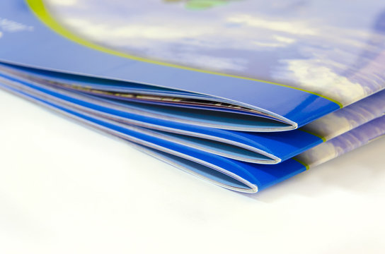 Stack of magazines, brochures, isolated on a white background.
