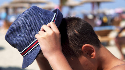 Young boy dazzled by summer sun on beach put on protection hat and smile to camera