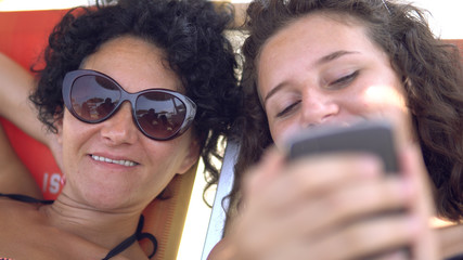 Mother and daughter list gallery of pictures on smartphone during summer holiday, cinematic dof