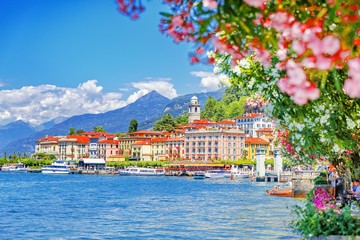 Wall Mural - Italy, Europe. Lake Como and lovely village Bellagio, view through pink flowers of oleander plant. Gorgeous travel background of traditional italian small towns, lake Como is popular summer resort.