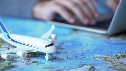Airplane model closeup, defocused person booking flight tickets online on laptop Fototapete