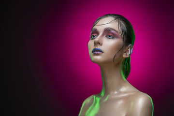 Beautiful young brunette wet model girl with naked shoulders on a pink gradient background. Vanguard conceptual makeup and hairstyle. Healthy clean skin.