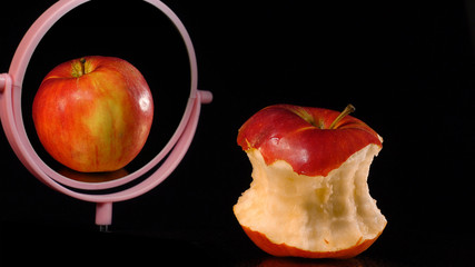 Concept of beauty and transfiguration. The apple stub looks into the mirror and dreams of becoming an apple.