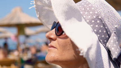 Beautiful woman on beach wear straw hat and glasses protection, look at distance and smile with blurred umbrelas at background
