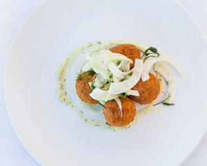 Flatlay of croquette on a white plate with fennel.