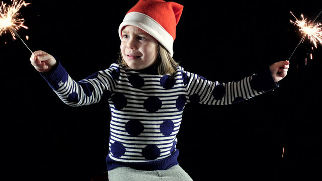A child, a girl of 4-5 years, was very much frightened of Christmas lights. Fear and horror in her eyes. Christmas sparklers. Dark background.