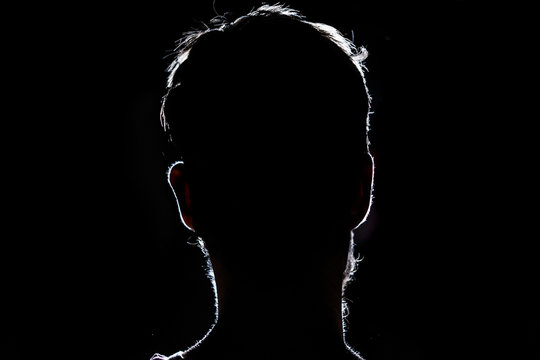 lighten portrait silhouette of a human head in the dark  background