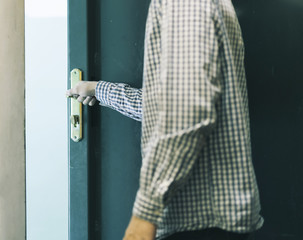 young male teenager in checkered shirt leaving home and closes door