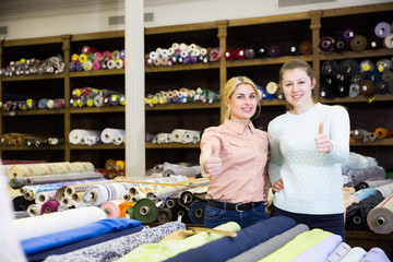 Two females gesturing thumbs up in fabric store