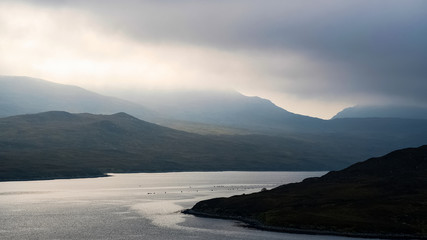 Sunlight piercing the clouds over Loch Shiphoirt, Isle of Lewis, Scotland, UK