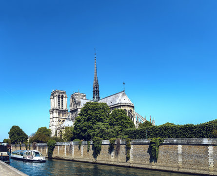 Notre Dame de Paris cathedral with cruise ship in Seine river in Paris, France
