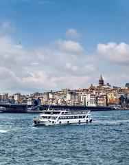 Istanbul, Tourist boat at Galata bridge with view of Galata tower to Golden Horn at background, Turkey