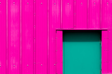 Modern industrialism. Neon pink building with green door. Vibrant paint color choice.