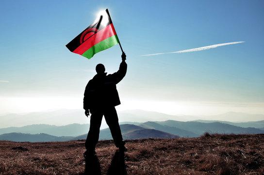 Successful silhouette man winner waving Malawi flag on top of the mountain peak