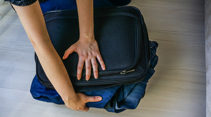 Closeup of young woman packing her suitcase at home. Girl struggling / trying to close suitcase full of clothes. Lady compressing overstuffed suitcase on floor. Holiday concept. Problem solving.