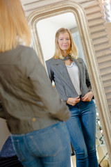 Lady in fitting room, looking at reflection in mirror