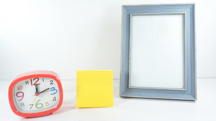 Blue wooden frame with red clock time 12.15 am. and note pad yellow on white background,copy space. .