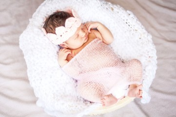 Cute Caucasian newborn infant baby girl asleep. Pink flower band on her head and pink plaid. Adorable newborn baby girl portrait studio stock image.