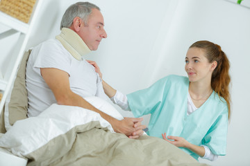 physiotherapist helping senior patient