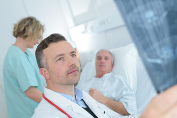 Doctor looking at xray, patient in background