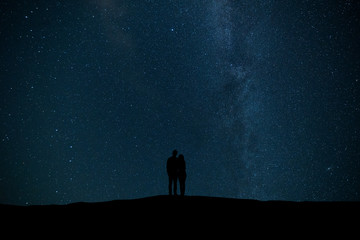 The couple standing on the starry sky background