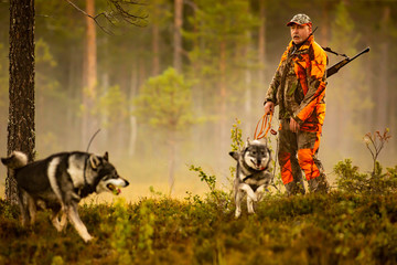 Acrylic Prints Hunting Hunter and hunting dogs chasing in the wilderness