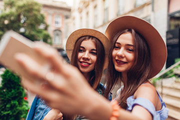 Outdoor portrait of two young beautiful women taking selfie using phone. Girls having fun in city. Best friends