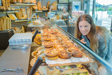 Lady in bakery looking in counter