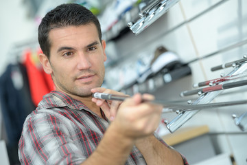male customer choosing drums and accessories in music shop