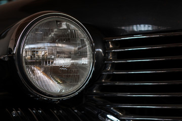 The headlight of an antique, rarity, vintage black car.