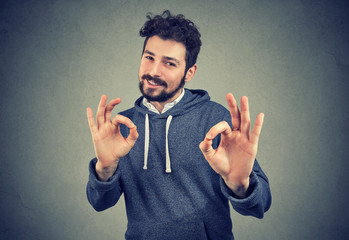 young handsome confident man showing ok sign
