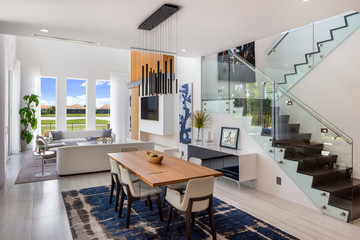 modern white open plan living and dining room with glass staircase