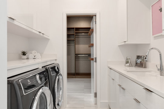 modern white laundry room with sink, washer, dryer looking into walk in wardrobe