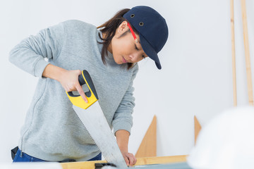 concentrated young female carpenter cutting wood