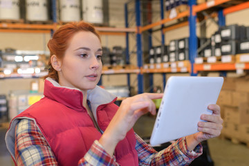 female manager using digital tablet in warehouse