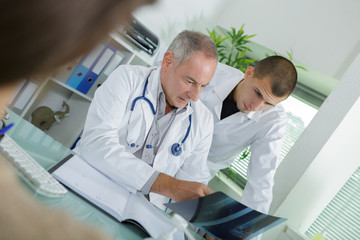 mature male doctor with assistant analyzing x-ray test