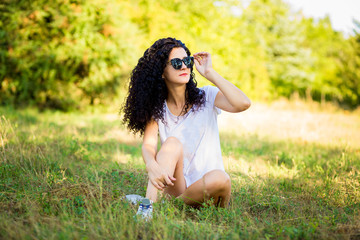 Pretty curly woman posing on grass in sunny day