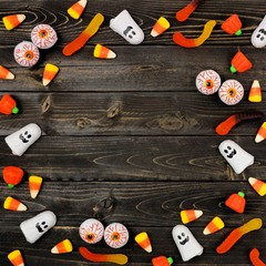 Halloween candy frame over a dark black wood background. Copy space.