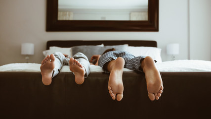 Close up of feet of couple sleeping on bed