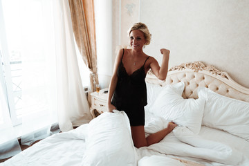 Girl smiles.The girl in the bed.Sexy blonde in black