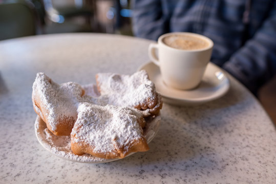 Beignets covered with powdered sugar, served with cafe au lait at the famous Cafe Du Monde in the French Quarter. Shallow focus on the powdered sugar for effect.