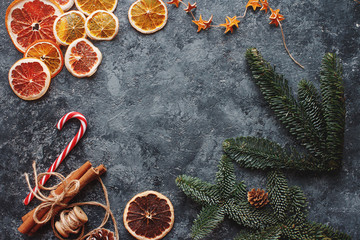 Christmas or New Year flat lay home decor, dry oranges, cinnamon, candies and fir branches on concrete background. Cozy winter homely scene, top view, copy space