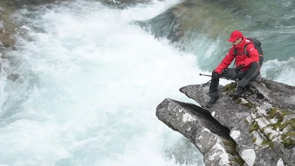 Wall Mural - Backpacker with Nordic Walking Poles Relaxing on the River Boulder. Slow Motion Footage