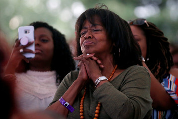 An attendee listens to live music during a free tribute concert to the late Aretha Franklin at Chene Park in Detroit