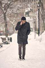 Millenial man on phone walking through park during winter